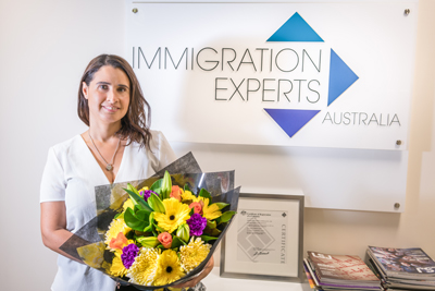 Migration agent Veronica receiving flowers as a thank you from a customer